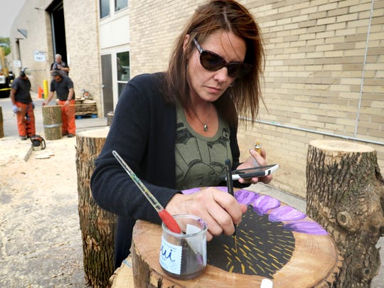 West Allis Artist Kendra Gordon uses a photo in her smartphone as reference as she paints a flower on a wood slab that will be turned into a table for the West Allis Downtown Business Improvement District (BID)  Wood & Wings! event set for Sept. 16 in the Visit West Allis downtown where artists will embellish log chairs made by West Allis Forestry department staff, and vendors will offer some of the best wings in West Allis.