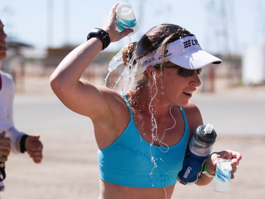 A runner tries to cool herself down at a water station