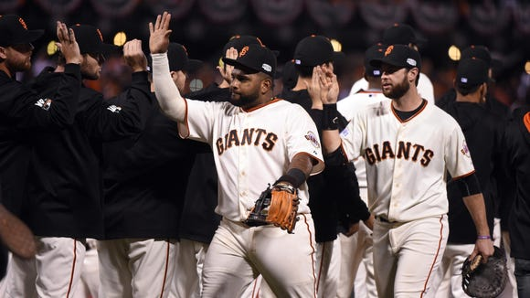 San Francisco Giants players including Pablo Sandoval (middle) celebrate on the field after defeating the Kansas City Royals during Game 5 on Sunday.