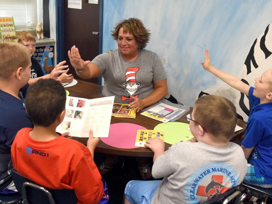 Tekoppel Elementary School teacher Ange Dierks gives high-fives to students in a guided reading rotation at the school in Evansville Wednesday.  Dierks has worked 26 years with the Evansville Vanderburgh School Corp., 23 of those have been at Tekoppel.