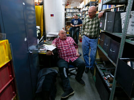 National Audio Company employees Monte Chaney (left), Bob Coverton (right) and Ray Massey are the engineers and mechanic getting the new audio cassette tape manufacturing machine up and running.