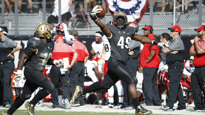 UCF's Seyvon Lowry recovers a fumble against Cincinnati in a game earlier this season.