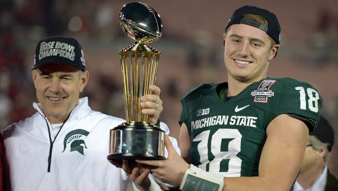 Michigan State coach Mark Dantonio and quarterback Connor Cook hoist the Leishman Trophy after the 100th Rose Bowl against Stanford on Jan. 1, 2014.
