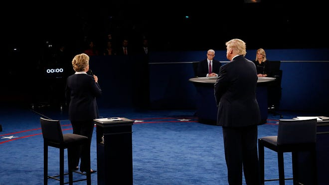 US Democratic presidential candidate Hillary Clinton speaks as US Republican presidential candidate Donald Trump listens during the second presidential debate at Washington University in St. Louis, Missouri, on October 9, 2016.