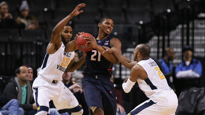 Illinois guard Malcolm Hill (21) is tied up by West Virginia guards Jevon Carter (2) and Tarik Phillip (12) during the first half.