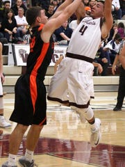 Tularosa's Cameron Sheppard, right, attempts a mid-range shot while being heavily guarded.
