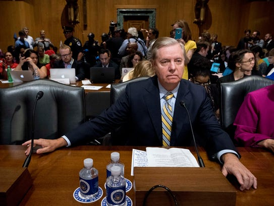 Sen. Lindsey Graham, R-S.C. waits as protesters are