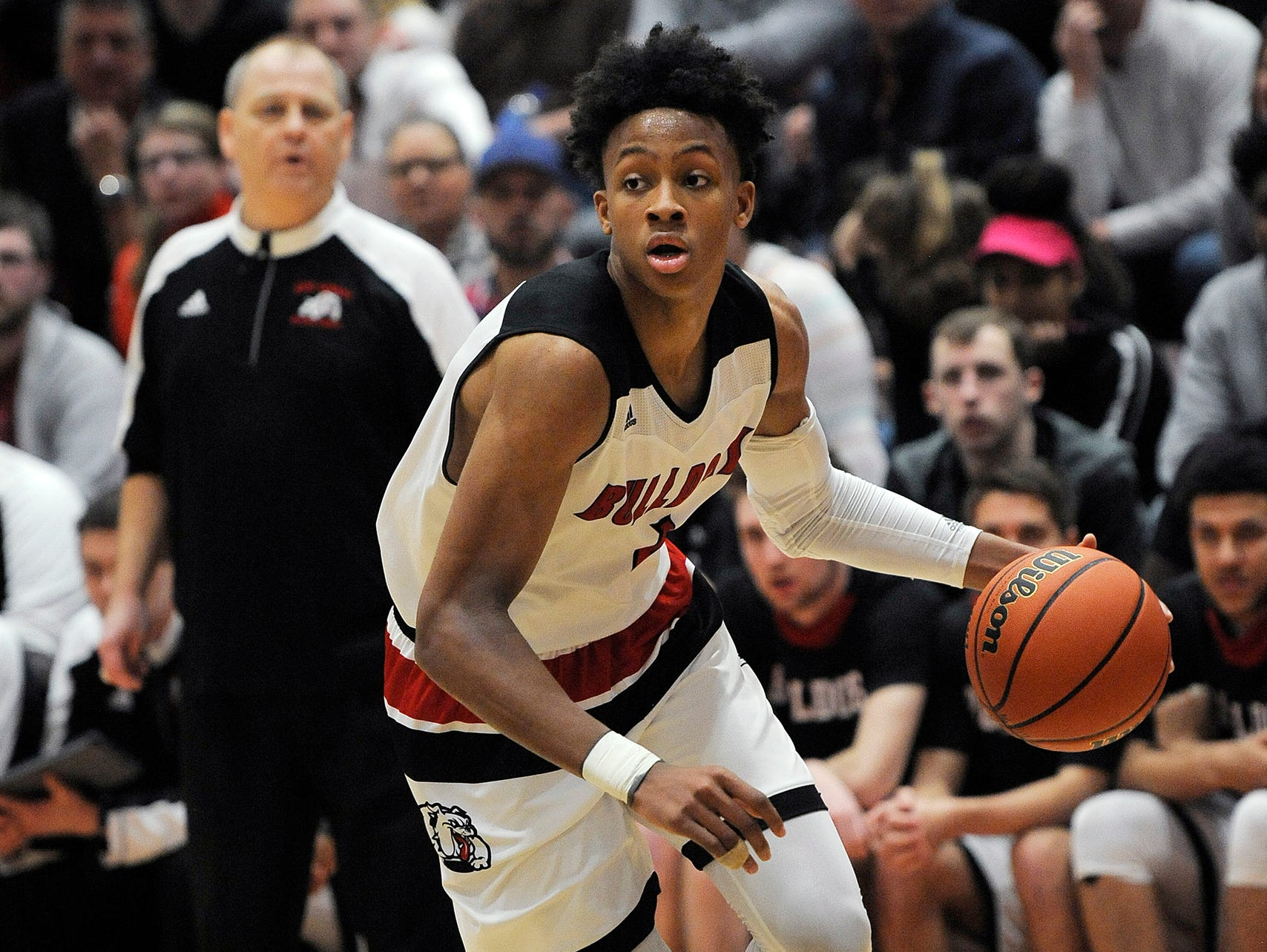 New Albany head coach Jim Shannon (in back) watches as Romeo Langford (1) drives against Providence on Friday at New Albany High School. New Albany won 55-40.