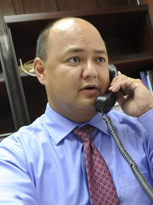 Department of Education Superintendent Jon Fernandez takes a call while at his desk at the Department of Education office in January 2013.