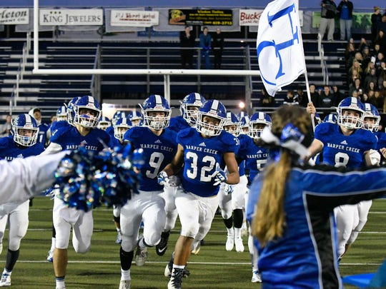 Harper Creek players take the field Friday night as the Beavers face off against rival Coldwater Cardinals.