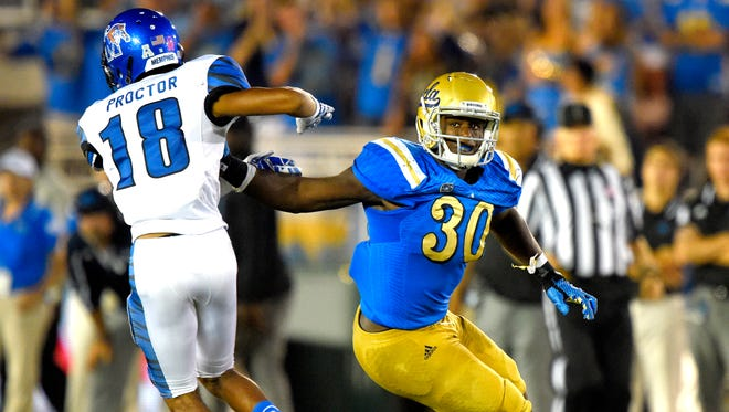 UCLA linebacker Myles Jack, right, keeps a hand on Memphis wide receiver Roderick Proctor during the second half of an NCAA college football game, Saturday, Sept. 6, 2014, in Pasadena, Calif. UCLA won 42-35. (AP Photo/Mark J. Terrill)