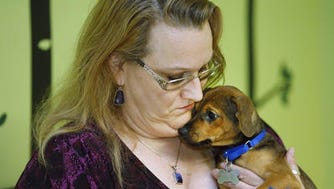 "Attorney Lisa Kiser comforts ""Rasin"" at Lost Our Home Pet Rescue in Tempe, Ariz. Kiser drafted a trust that helped secure care for a deceased woman's animals."