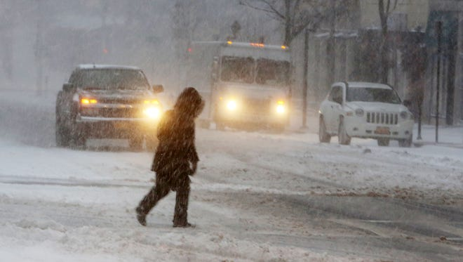 A pedestrian fights the wind-blown snow while crossing Mamaroneck Avenue in White Plains on Saturday.