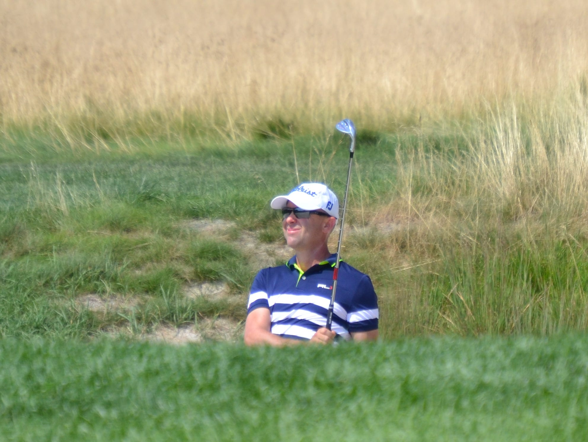 Rob Labritz watches his ball settle 15 feet past the hole on the 16th green Thursday after blasting out from a bunker.