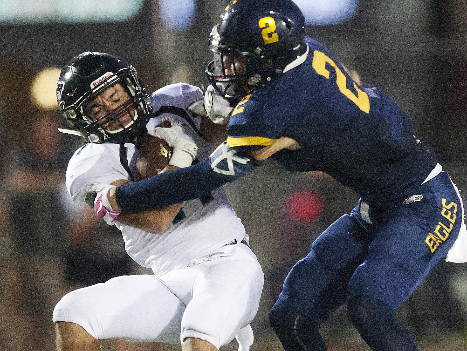 Naples High School's Chris Riley, right, tackles Gulf Coast's Daniel Rendon for a loss Friday at Naples High School.