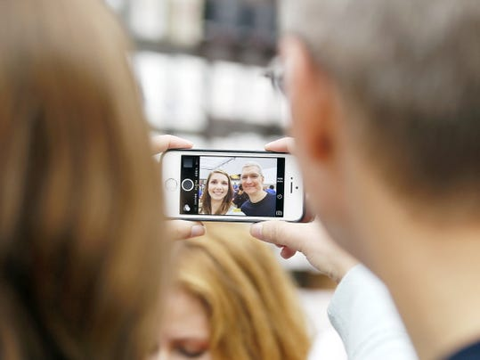 Apple CEO Tim Cook, right, takes a photo with an Apple employee during the launch and sale of the new iPhone 6 on Sept. 19, 2014, at an Apple store in Palo Alto, Calif.