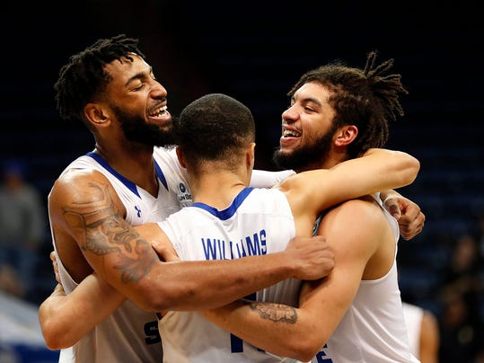Georgia State forward Jordan Session, left, guard D'Marcus Simonds, right, and guard Isaiah Williams, center, celebrate in the final minute of the second half in their victory over Texas-Arlington in the the Sun Belt Conference NCAA college basketball championship game in New Orleans, Sunday, March 11, 2018. Georgia State won 74-61. (AP Photo/Gerald Herbert)