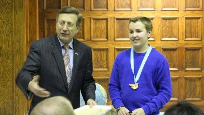Dylan Hankel of Memorial Middle School is shown with Mayor Mike Huether during a reading of his Human Rights Day essays on Wednesday night in Sioux Falls.