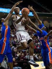 Texas A&M guard Duane Wilson (13) drives the lane against Savannah State forward John Grant Jr. (4), guard Jahir Cabeza (30) and guard Zach Sellers (3) during the first half of an NCAA college basketball game Wednesday, Dec. 13, 2017, in College Station, Texas. (AP Photo/Sam Craft)