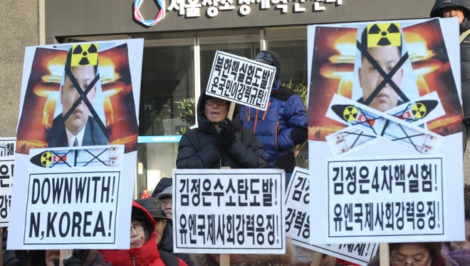 South Korean protesters with defaced photos of North Korean leader Kim Jong Un stage a rally during a rally against North Korea's announcement that it had tested a hydrogen bomb in Seoul, South Korea, Thursday, Jan. 7, 2016.