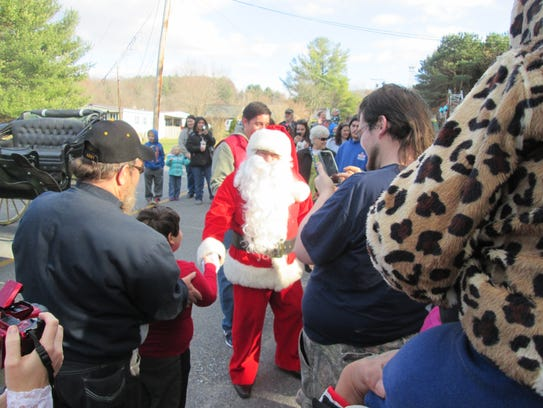 Santa steps out of the carriage to greet his fans.