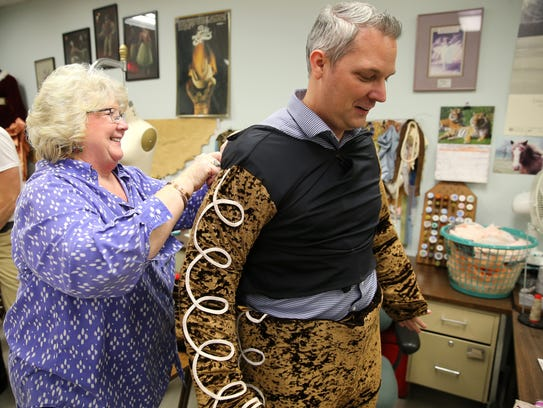 Wardrobe mistress Diana Vandergriff-Adams helps Eric