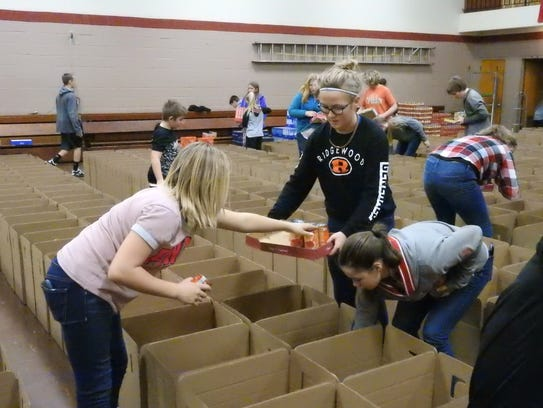 Kelley Maslowski offers cans to classmates in packing