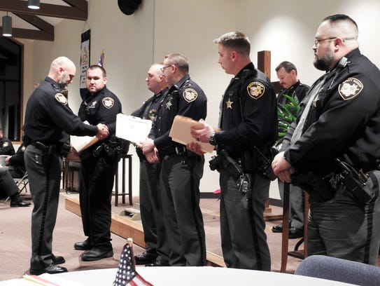 Lt. Dean Hettinger hands out certificates and shakes