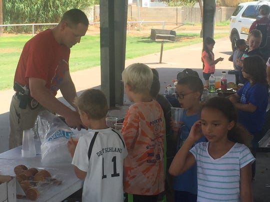Alamogordo police Capt. Michael Lawrence helped cook the over 100 hot dogs served to the Boys and Girls Club of Otero County children.