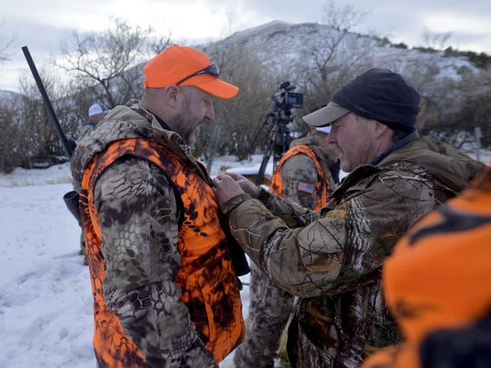Jon Dodson, a camera man for the Grateful Nation television show, puts a wireless microphone on Shane Briel, an Army veteran, during the Field and Dreams Purple Heart Veterans Hunt on the McKamey Ranch near Ulm