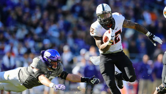 Oklahoma State running back Chris Carson (right) eludes a TCU defender during a game last season.
