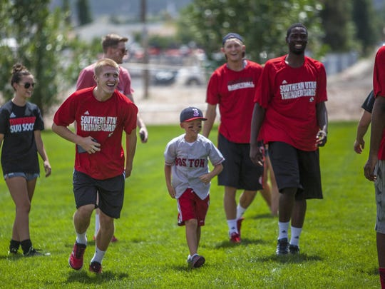 SUU athletes share a laugh with a child during a game of soccer at the Watermelon Bust on Saturday.