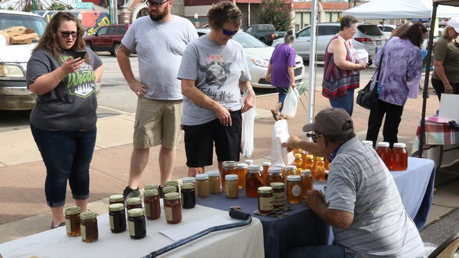 Deleah Hanley, from left, Josh Hanley and Deanna Hanley purchase pure, raw honey from Earl Hardin during a visit to the Fort Smith Farmers Market, Saturday, June 27, 2020.