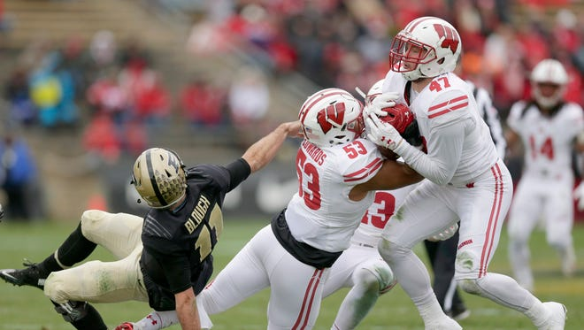 Badgers linebackers T.J. Edwards  (left) and Vince Biegel secure the ball after Edwards intercepted Purdue quarterback David Blough on Saturday in the second quarter of Wisconsin's 49-20 win over the Purdue Boilermakers at Ross-Ade Stadium in West Lafayette, Ind.