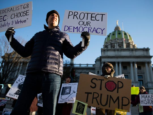 Protesters demonstrate ahead of Pennsylvania's 58th Electoral College at the state Capitol in Harrisburg, Pa., Monday, Dec. 19, 2016. The demonstrators were waving signs and chanting in freezing temperatures Monday morning as delegates began arriving at the state Capitol to cast the state's electoral votes for president.