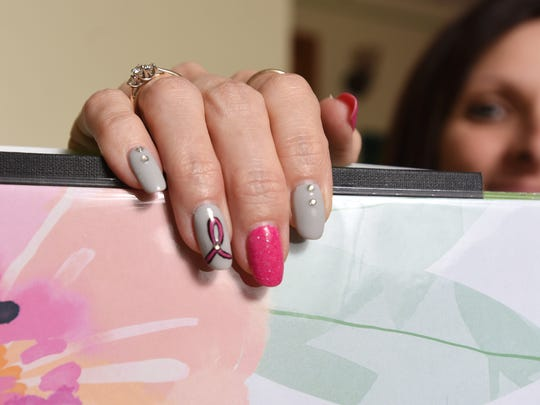 Kimberly Alexander's ring finger has a pink ribbon