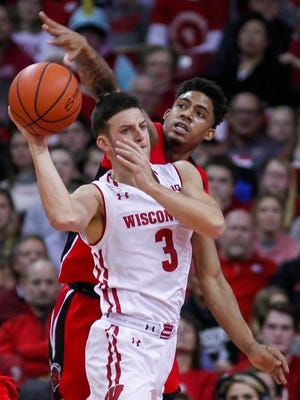 Rutgers' Corey Sanders, behind, reaches for the ball held by Wisconsin's Zak Showalter during the first half on Tuesday in Madison, Wis.