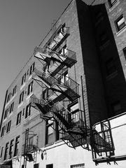 A fire escape and its shadows as seen from a parking lot of the Columbus Building (50 Chestnut Street).