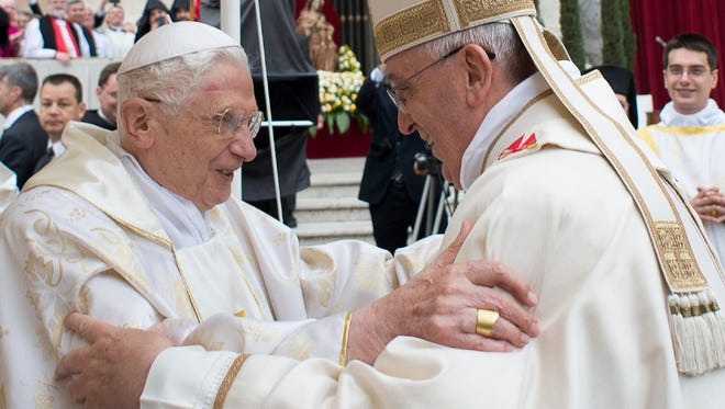 Vatican handout picture shows Pope Francis, right, meeting with Pope emeritus Benedict XVI during canonization mass Sunday.