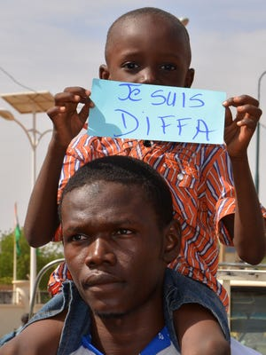"""A boy holds a sign reading """"I am Diffa"""" during a protest march in Niamey on June 4, 2016, against Boko Haram-related violence in the southeast of Niger."""