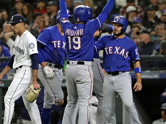 Seattle Mariners closing pitcher relief pitcher Edwin Diaz, left, walks back to the mound after covering home as Texas Rangers' Jurickson Profar (19) celebrates with teammates as he scored on a three-run double hit by Rougned Odor during the ninth inning of a baseball game Tuesday, May 29, 2018, in Seattle.