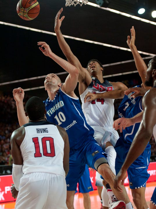 Finland's Tuukka Kotti, second left,  tries to dunk on the basket between United States's  Kyrie irving, left, and Anthony Davis, second right, during the Group C Basketball World Cup match between United States and Finland,  in Bilbao northern Spain, Saturday, Aug. 30, 2014. The 2014 Basketball World Cup competition will take place in various cities in Spain from Aug. 30 through to Sept. 14. (AP Photo/Alvaro Barrientos)