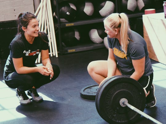 Coach Taylor Whitson shares a moment with a fellow enthuasiast following a workout at CrossFit Cedar City.