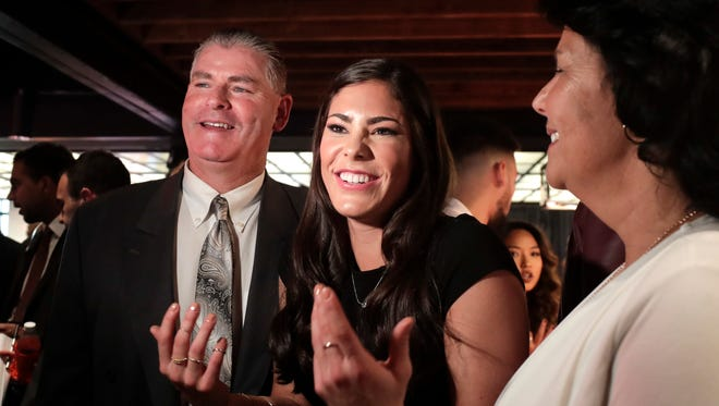 Washington guard Kelsey Plum (center) speaks to a television crew alongside her father, Jim, and mother, Katie, before the WNBA draft Thursday.