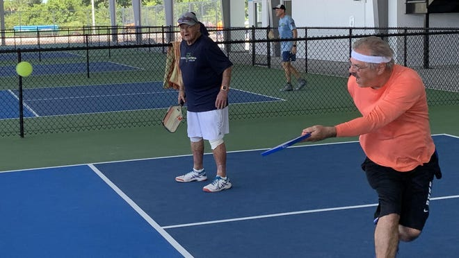 Daytona Beach resident Al Heilman, right, makes an underhand shot while his pickleball doubles partner Myckey Phelan, also of Daytona Beach, watches on one of the covered courts at the new Pctona at Holly Hill complex at 1060 Ridgewood Ave. last week. The 24-court complex opens to the general public on July 15.