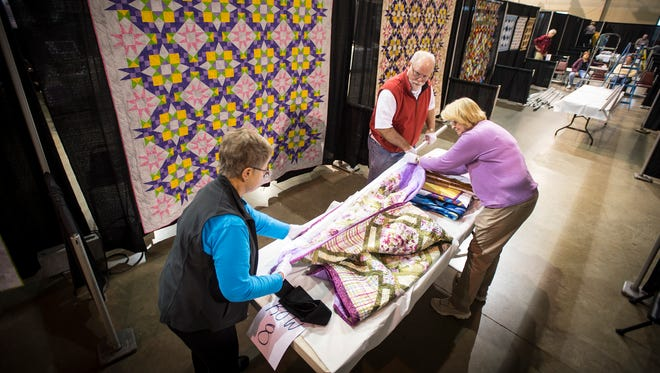 Peggy Over, Barbara  Kuhlengel and  John Over prepare quilts to be hung at the Lebanon Expo Center for the Lebanon Quilters Guild 11th Annual Exhibition of Quilts, Nov. 10 and 11.