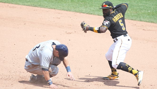 Pirates second baseman Josh Harrison throws to first base after a force out of Brewers shortstop Tyler Saladino at second during the fifth inning of Game 1 at PNC Park.