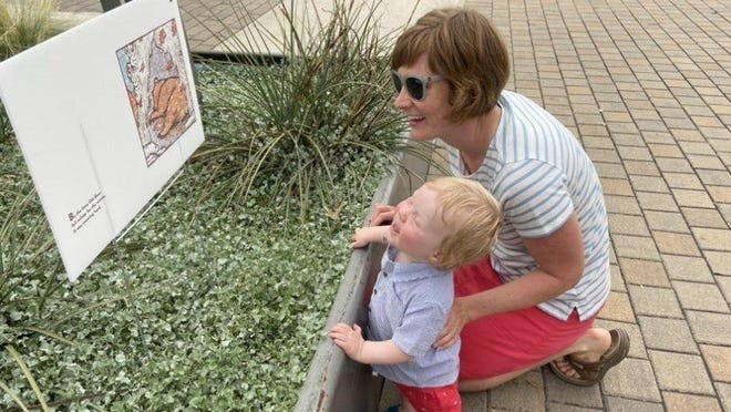 Cate and Cormac Sweeney enjoying a StoryWalk outside the Bee Cave Public Library.