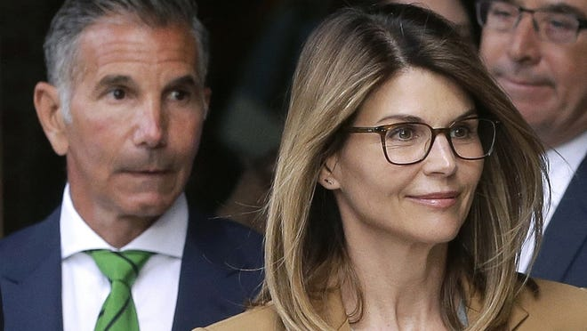 Lori Loughlin and her husband, Mossimo Giannulli, depart federal court in Boston in 2019.  Both have been sentenced in connection with a nationwide college admissions bribery scandal.