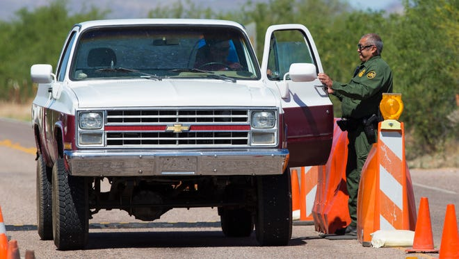 A Border Patrol agent stops a car at a checkpoint on Arivaca Rd., about 20 miles northeast of Arivaca, Ariz.